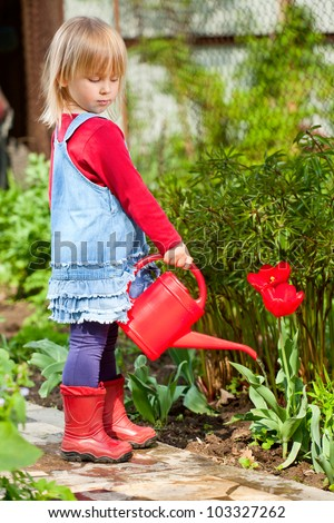 Little girl watering red tulip with red watering can