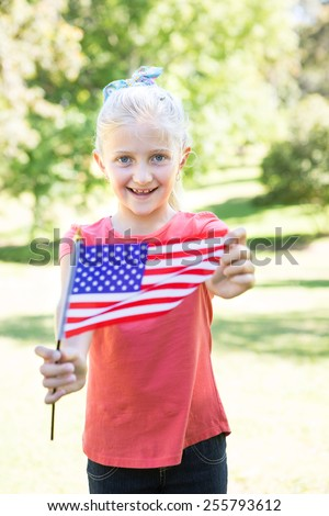 Little girl waving american flag on a sunny day - stock photo