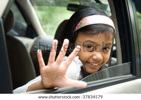 Little girl waving goodbye from inside of a car - stock photo