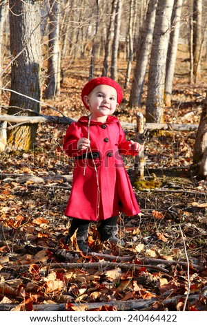 Little girl wearing a red coat and hat in the forest - stock photo