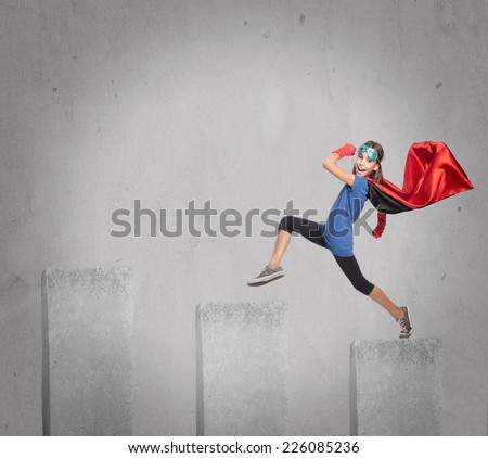 little girl wearing a superhero costume walking on a growing chart - stock photo