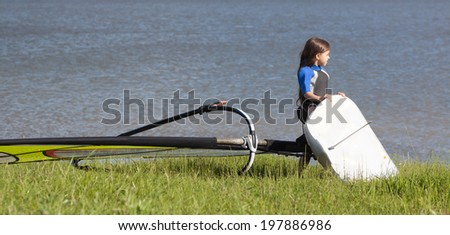 Little girl wearing an equipment to the water, ready for windsurfing - stock photo