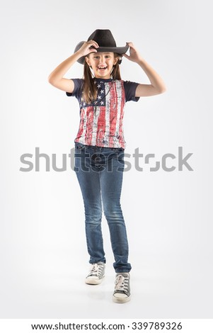 Little girl wearing cowboy costume standing with folded hands, over white background - stock photo