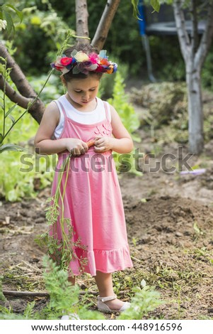 Little girl wearing flower wreath harvesting carrots from backyard garden. Healthy lifestyle concept