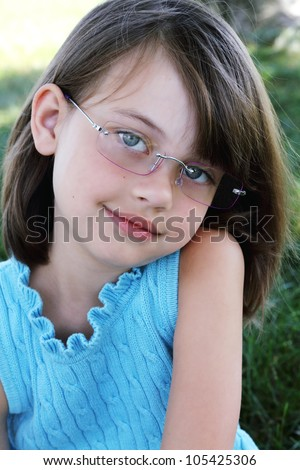 Little girl wearing glasses and looking directly at viewer. Shallow depth of field with selective focus on child's face. - stock photo