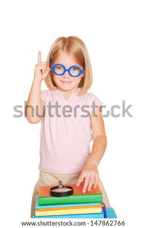 Little girl wearing glasses with books and magnifying glass pointing index finger up, playing as a teacher, ready for your text, logo or symbols. Isolated on white background - stock photo