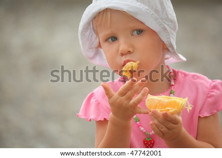 little girl wearing panama hat is eating orange. focus on right hand. - stock photo