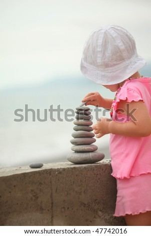 little girl wearing pink dress and white panama hat is building a construction from pebble stones. - stock photo