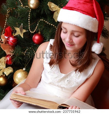 little girl wearing red and white santa's hat and holding old fashion book on Vintage theme