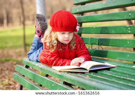 Little girl wearing red reading book on a bench in the park. - stock photo