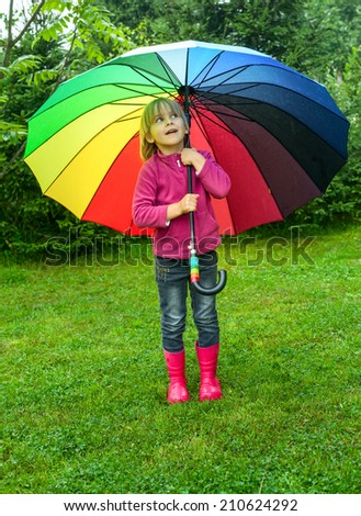 Little girl wearing red rubber boots hiding behind colorful umbrella in the rain - stock photo