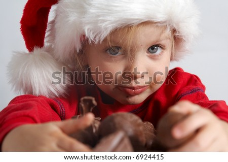 Little girl wearing red Santa hat eating chocolate - stock photo