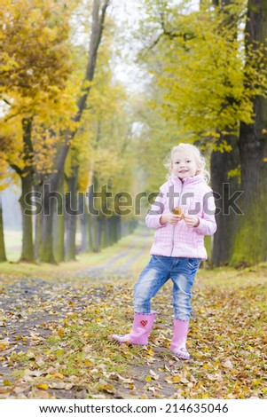 little girl wearing rubber boots in autumnal alley - stock photo