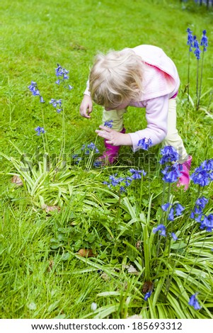 little girl wearing rubber boots in garden - stock photo