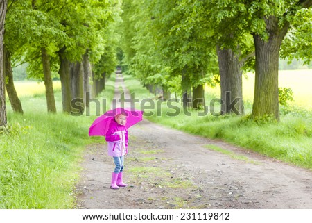 little girl wearing rubber boots with ubrella in spring alley - stock photo
