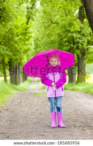 little girl wearing rubber boots with umbrella in spring alley - stock photo