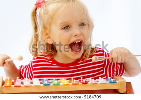 Little girl wearing striped red t-shirt playing the rainbow xylophone - stock photo
