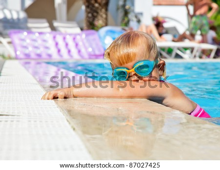 Little girl wearing swimming goggles in a hotel pool - stock photo