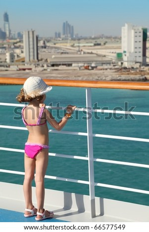 little girl wearing swimming suit and hat is standing on deck of cruise ship and looking at city. - stock photo