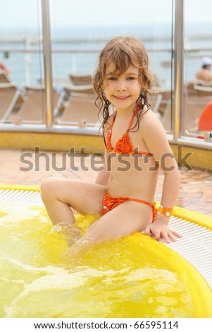 little girl wearing swimming suit sitting on edge of swimming pool - stock photo