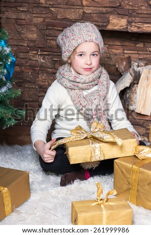 Little girl wearing winter hat and scarf posing near fireplace and christmas presents - stock photo