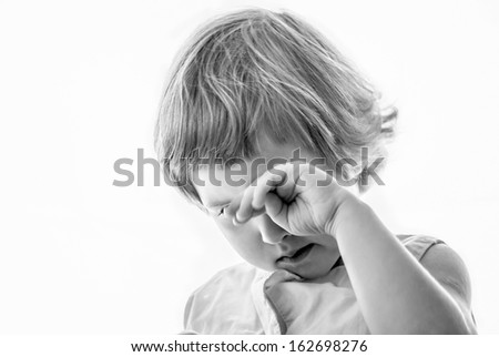 Little girl wiping her eyes - stock photo