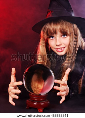 Little girl witch holding crystal ball. - stock photo