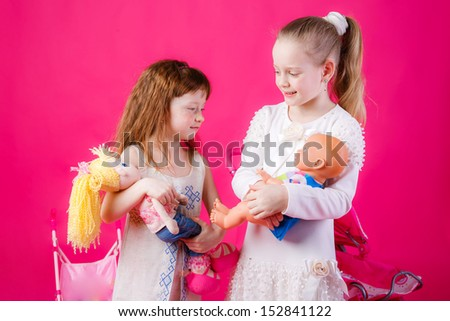 little girl with a baby carriage and doll - stock photo