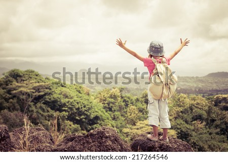 little girl with a backpack standing on a mountain top at the day time - stock photo