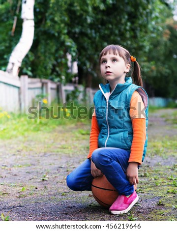Little girl with a ball in the park. - stock photo