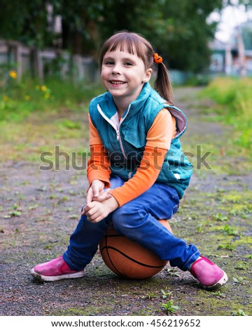 Little girl with a ball in the park.