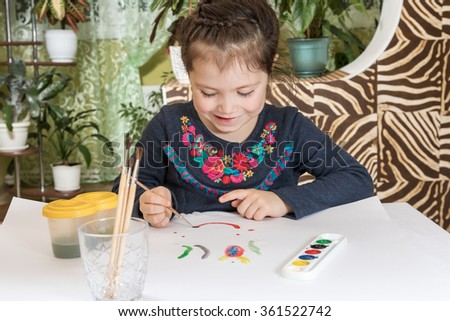 Little girl with a brush draws on a white sheet smiling - stock photo