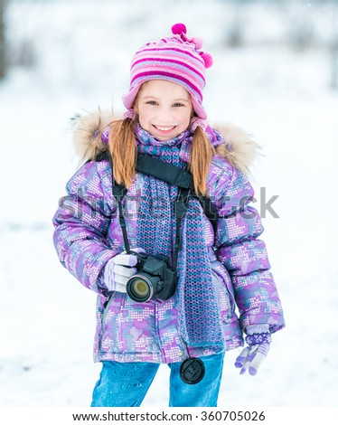 little girl with a camera in the winter park - stock photo