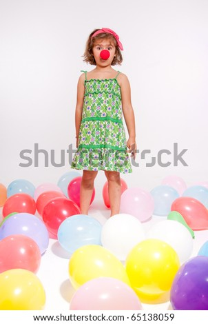 Little girl with a clown nose surrounded by balloons - stock photo