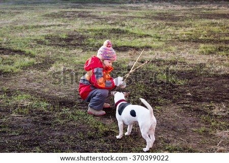 little girl with a dog playing with wooden sticks - stock photo