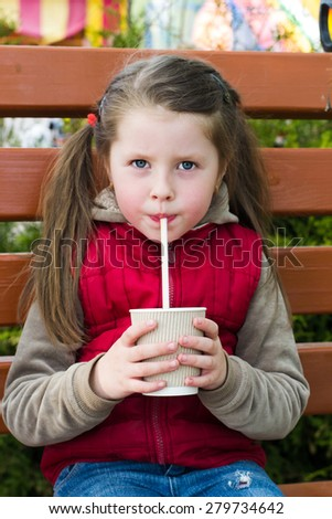 little girl with a drink with a serious view on a park bench - stock photo