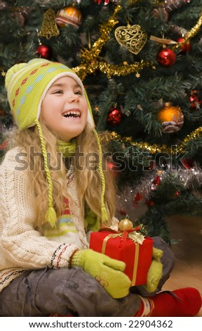 Little girl with a gift, blurred Christmas tree as background - stock photo