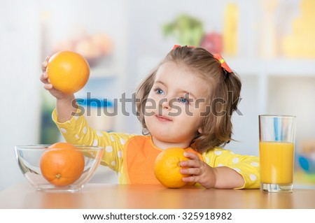 Little girl with a glass of juice and oranges