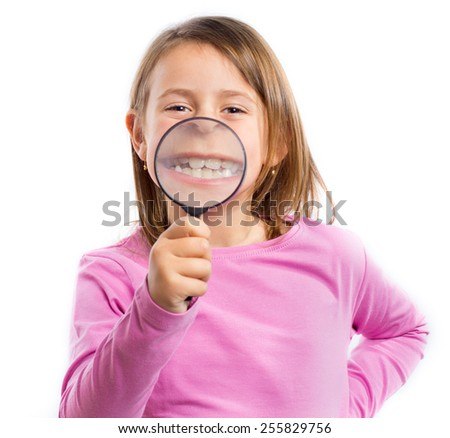 Little girl with a magnifying glass in front of her mouth - stock photo