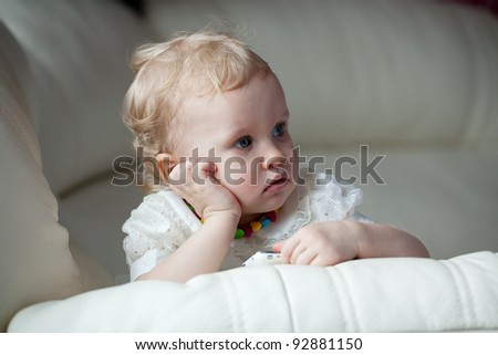 Little girl with a phone in thought settled on the couch - stock photo