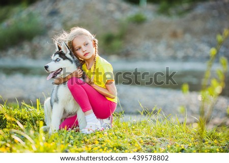 Little girl with a puppy husky, outdoor summer