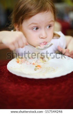 Little girl with a surprised expression on her face eating spaghetti in a cafe