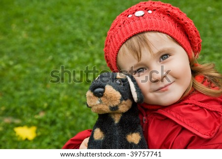 little girl with a toy dog in park - stock photo