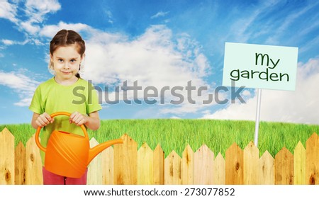 Little girl with a watering can next to fence of the garden - stock photo