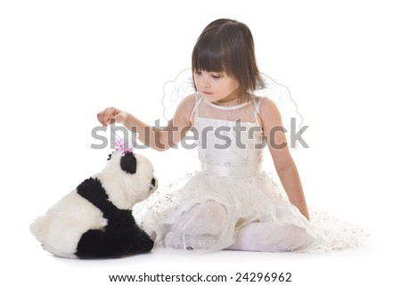 Little girl with angel wings casting spell on a panda