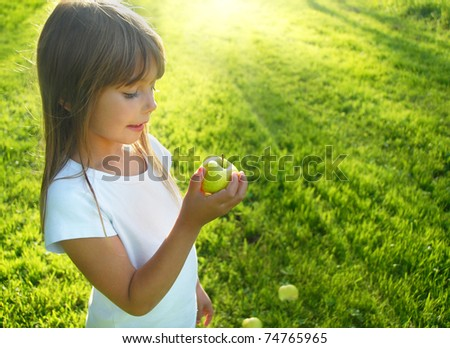 Little girl with apple in the garden - stock photo