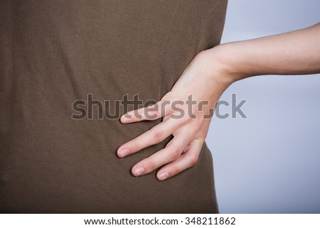 Little girl with back pain holding the hand isolated on white background.Little girl suffers from backache.