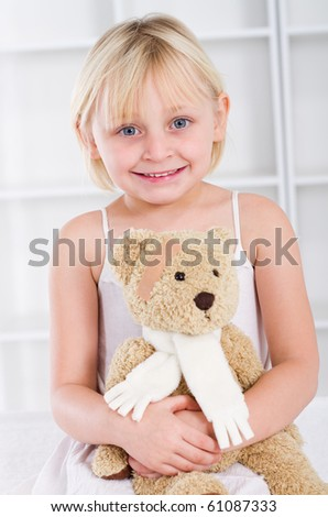 Little girl with band-aid on her face holding a teddy bear - stock photo