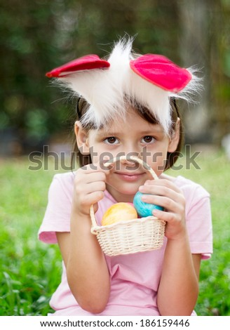 Little girl with basket of colored easter eggs - stock photo