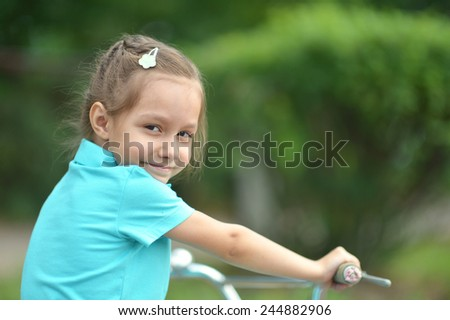 Little girl with bicycle outdoors in summer - stock photo